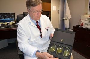 Dr. Bill Bigham holds models of  intraocular lenses.
