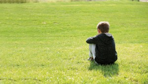 Sad abandoned orphan sitting in nature and contemplating, autism