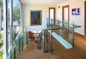 Christian Rice's contemporary interior of a home on Cajon Place features a central steel-frame and glass stairwell; it is visually separated from the home's main living space with a slatted wood wall, which artfully defines the dining space.