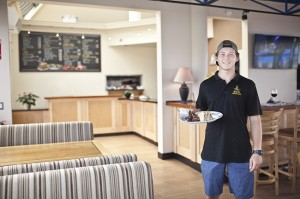 Server Leland Orr delivers a plate of Greek specialties in the newly remodeled restaurant. photo by Kristen Vincent Photography