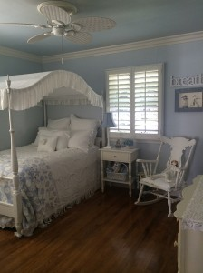 Boulanger created a coastal cottage feel with white cabinets in the kitchen and pastel colors in the bedroom.
