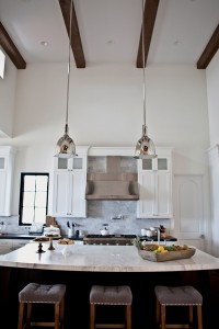 White walls and exposed wood beams add a Mediterranean touch in the kitchen designed by Bungalow 56.