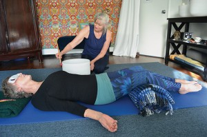 Lulu Martin enhances her private yoga session with longtime client and friend Caroline Murray through the use of crystal bowls, providing a resonance that connects with the body's chakras.