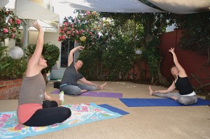 Danell Dwaileebe, right, leads a yoga stretch session in the courtyard patio at Discover Wellness, which is her studio.